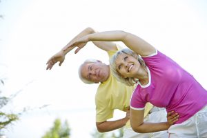 Active senior couple doing side bends
