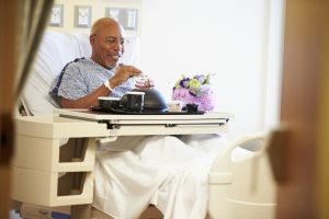 Senior Male Patient Enjoying Meal In Hospital Bed